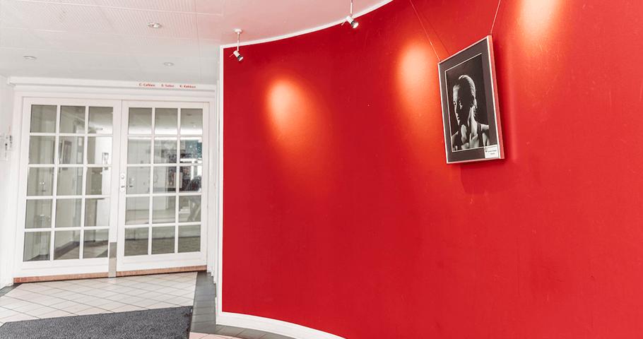 Husets Foyer med indgang til salen og den smukke røde bue med kunst udstillet. Foto: Kenneth Jensen.