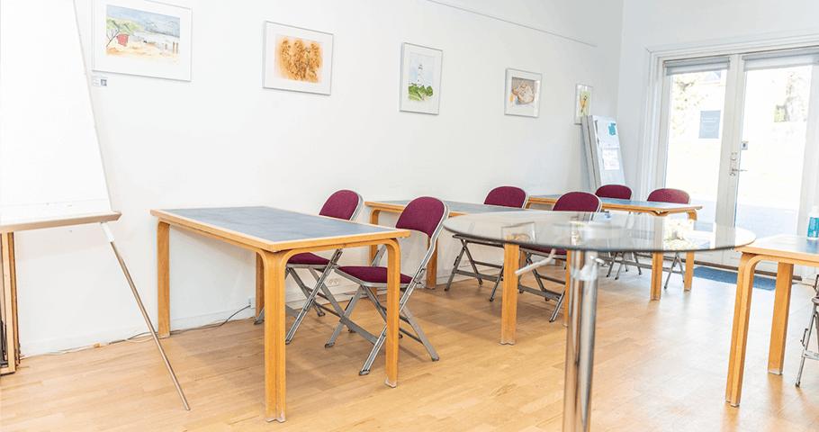 Lille mødelokale med borde, stole og talerbord. Foto: Kenneth Jensen.